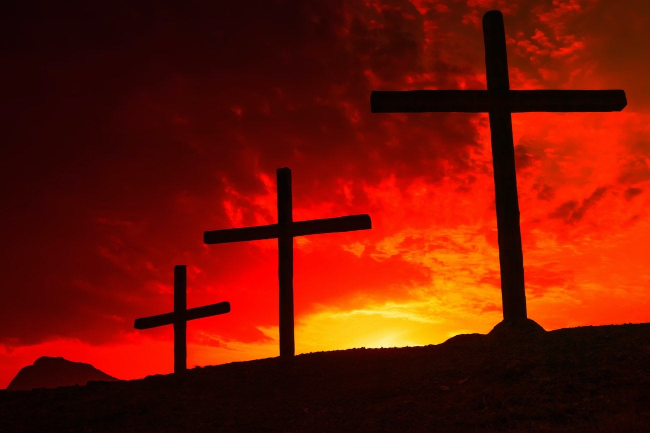Three crosses on the background of the sunset red-yellow sky. The concept of the crucifixion of Jesus.
